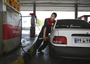 Photo - A gas station worker fills a car in central Tehran, Iran, Friday, April 25, 2014.  The Iranian government on Friday cut a portion of fuel subsidies, nearly doubling some prices at the pump as part of a second round of cuts delayed since 2012. (AP Photo/Vahid Salemi)