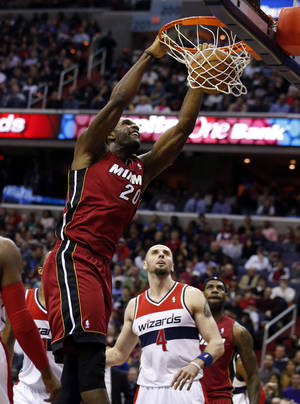 Photo - Miami Heat center Greg Oden (20) dunks the ball in front of Washington Wizards center Marcin Gortat (4), from Poland, in the first half of an NBA basketball game on Wednesday, Jan. 15, 2014, in Washington. It was Oden's first NBA regular-season game in more than four years. (AP Photo/Alex Brandon)