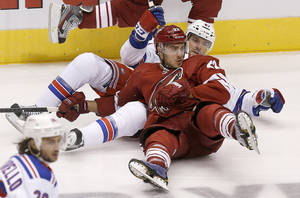 Photo - New York Rangers' Benoit Pouliot (67) takes down Phoenix Coyotes' Lucas Lessio (22) but is called for a holding penalty in the first period during an NHL hockey game on Thursday, Oct. 3, 2013, in Glendale, Ariz. (AP Photo/Ross D. Franklin)