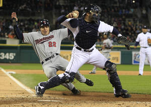 Photo -   Detroit Tigers catcher Alex Avila throws to first as Minnesota Twins' Matt Carson is out at home during the fifth inning of the second baseball game of a doubleheader at Comerica Park in Detroit, Sunday, Sept. 23, 2012. (AP Photo/Carlos Osorio)