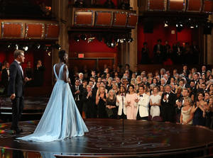 "Photo - Lupita Nyong'o receives a standing ovation as she accepts the award for best actress in a supporting role for ""12 Years a Slave"" during the Oscars at the Dolby Theatre on Sunday, March 2, 2014, in Los Angeles.  (Photo by Matt Sayles/Invision/AP)"
