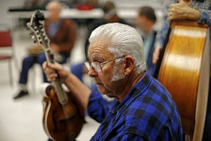 Photo - Ron Reser, of Shawnee, listens during a bluegrass jam session in Del City.