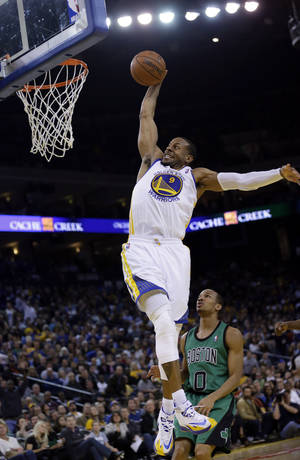 Photo - Golden State Warriors' Andre Iguodala (9) goes up for a dunk next to Boston Celtics' Avery Bradley (0) during the second half of an NBA basketball game on Friday, Jan. 10, 2014, in Oakland, Calif.  Golden State won 99-97. (AP Photo/Marcio Jose Sanchez)