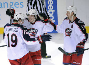 Photo - Columbus Blue Jackets Ryan Johansen (19) celebrates with Matt Calvert, center, and Brandon Dubinsky (17) after Johansen scored the game-winning goal during a shootout in an NHL hockey game against the Buffalo Sabres in Buffalo, N.Y., Saturday, Jan.18, 2014. Columbus won 4-3. (AP Photo/Gary Wiepert)