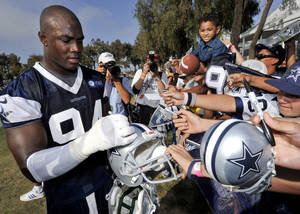 photo - Dallas Cowboys linebacker DeMarcus Ware signs autographs at the conclusion of NFL football training camp, Monday, July 30, 2012, in Oxnard, Calif. (AP Photo/Gus Ruelas) ORG XMIT: LAD121