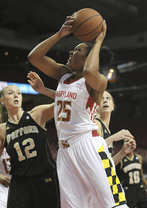 Photo - Maryland's Alyssa Thomas, right, shoots as Wofford's Lauren Kirby defends  in the first half of an NCAA college basketball game Saturday, Dec. 28, 2013, in College Park, Md. (AP Photo/Gail Burton)