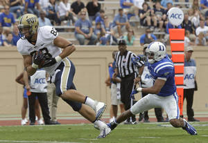 Photo - Duke's Ross Cockrell (6) misses the tackle as Pittsburgh's Scott Orndoff (83) scores a touchdown during the second half of an NCAA college football game in Durham, N.C., Saturday, Sept. 21, 2013. Pittsburgh won 58-55. (AP Photo/Gerry Broome)