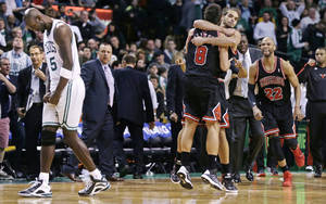 photo - As Boston Celtics forward Kevin Garnett, left, walks off the court, Chicago Bulls guard Marco Belinelli (8) is congratulated by teammate Joakim Noah taking an overtime win in an NBA basketball game in Boston Friday, Jan. 18, 2013.  Belinelli hit the go ahead basket less than 5 seconds on the clock. The Bulls beat the Celtics 100-99. (AP Photo/Charles Krupa)