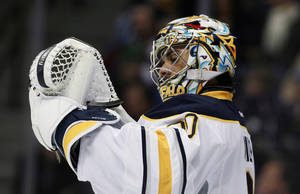 Photo - Buffalo Sabres goalie Ryan Miller checks his glove after giving up goal to the Colorado Avalanche in the second period of an NHL hockey game in Denver, Saturday, Feb. 1, 2014. (AP Photo/David Zalubowski)
