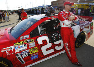 Photo - Kevin Harvick stands next to his race car after qualifying for Sunday's NASCAR Sprint Cup series auto race at Kansas Speedway in Kansas City, Kan., Friday, Oct. 4, 2013. Harvick won the pole. (AP Photo/Colin E. Braley)