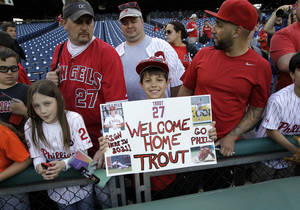 Photo - Justin Shephard, nine years old, from Deptford, N.J., holds up a sign for Los Angeles Angels' Mike Trout before the start of a baseball game with the Philadelphia Phillies, Tuesday, May 13, 2014, in Philadelphia. (AP Photo/Laurence Kesterson)