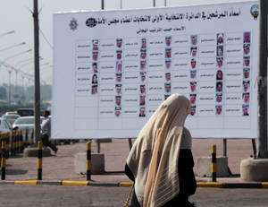 photo -   A Kuwaiti woman walks past a board with the names and photos of next December's election candidates in Salwa, Kuwait, Sunday, Nov. 25, 2012. There is little middle ground but plenty of high-stakes tension as Kuwait stumbles toward elections for the most politically empowered parliament among the Gulf Arab states. (AP Photo/Gustavo Ferrari)