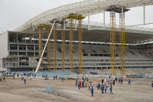 Photo - Construction workers return to the Arena Corinthians stadium that will host the opening match of the World Cup, five days after an accident killed two workers, in Sao Paulo, Brazil, Monday, Dec. 2, 2013. Construction company Odebrecht had suspended work on the site after a crane collapsed on Wednesday, Nov. 27, as it was hoisting a 500-ton piece of roofing. (AP Photo/Andre Penner)