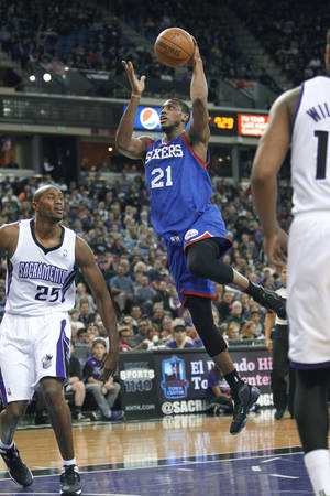 Photo - Philadelphia 76ers forward Thaddeus Young (21) drives to the basket against Sacramento Kings defender Travis Outlaw (25) during the first half of an NBA basketball game in Sacramento, Calif., on Thursday, Jan. 2, 2014. (AP Photo/Steve Yeater)