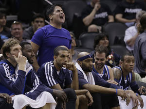 Photo - Dallas Mavericks owner Mark Cuban, top, cheers from behind the team's bench during the second half of Game 2 of the opening-round NBA basketball playoff series against the San Antonio Spurs, Wednesday, April 23, 2014, in San Antonio. Dallas won 113-92. (AP Photo/Eric Gay)