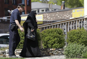 Photo - A police officer escorts a woman in Muslim dress into an entrance to the Graham, Putnam, at Mahoney Funeral Parlors in Worcester, Mass., Monday, May 6, 2013 where the body of slain Boston Marathon bombing suspect Tamerlan Tsarnaev is being prepared for burial. Funeral director Peter Stefan has pleaded for government officials to use their influence to convince a cemetery to bury Tsarnaev, but so far no state or federal authorities have stepped forward. (AP Photo/Elise Amendola)