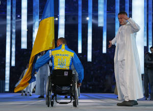 Photo - Biathlete Mykhaylo Tkachenko, representing Ukraine, enters the arena during the opening ceremony of the 2014 Winter Paralympics at the Fisht Olympic stadium in Sochi, Russia, Friday, March 7, 2014. (AP Photo/Dmitry Lovetsky)