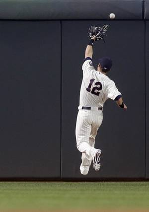 Photo - Minnesota Twins right fielder Chris Herrmann misses the catch as Detroit Tigers' Austin Jackson gets a triple during the first inning of a baseball game, Wednesday, Sept. 25, 2013, in Minneapolis. (AP Photo/Jim Mone)