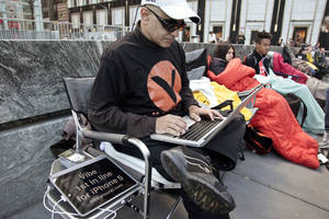 Photo - Hazen Sayer, an app developer, is first in line outside Apple's Fifth Avenue store Thursday in New York.  Sayer started camping out a week ago to be one of the first to get the new iPhone 5, which will go on sale in the U.S. and eight other countries Friday.  AP Photo <strong>Bebeto Matthews</strong>