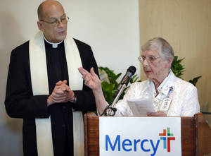 Photo -  The Rev. Ray Ackerman, of St. John the Baptist Catholic Church and Sister of Mercy Rose Power say a prayer during a blessing ceremony to the facilities in the newly opened Edmond Mercy center on Wednesday. Photo by Chris Landsberger, The Oklahoman  <strong>CHRIS LANDSBERGER -   </strong>