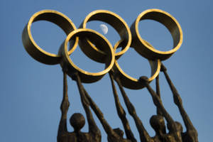 Photo - The moon is visible through a statue with  the Olympic rings during the executive board's meeting, next to the IOC headquarters, in Lausanne, Switzerland, Tuesday, Dec.  10, 2013.  (AP Photo/Keystone,Jean-Christophe Bott)