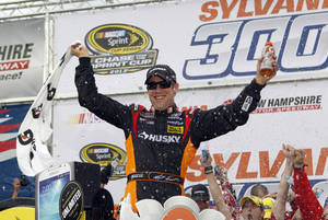 Photo - NASCAR driver Matt Kenseth celebrates in Victory Lane after winning the NASCAR Sprint Cup Series auto race at New Hampshire Motor Speedway, Sunday, Sept. 22, 2013, in Loudon, N.H. (AP Photo/Mary Schwalm)