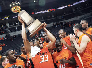 photo - OSU's Marshall Moses raises the All-College Classic trophy after the Cowboys beat La Salle 77-62 Monday night at the Ford Center.  PHOTO BY NATE BILLINGS, THE OKLAHOMAN