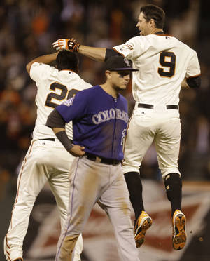 Photo - San Francisco Giants' Brandon Belt (9) and Hector Sanchez, left, celebrate as Colorado Rockies' Troy Tulowitzki, center, walks off the field after Belt had the game winning hit in the tenth inning of a baseball game Monday, Sept. 9, 2013, in San Francisco. (AP Photo/Ben Margot)