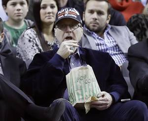 Photo - Portland Trail Blazers owner Paul Allen watches from his seat under the basket during the second half of an NBA basketball game against the Denver Nuggets in Portland, Ore., Thursday, Jan. 23, 2014.  Portland Won 110-105. (AP Photo/Don Ryan)