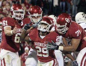 Photo - klahoma running back Chris Brown, center, celebrates with teammates after his touchdown against Texas A&M in the second quarter of an NCAA college football game in Norman, Okla., Saturday, Nov. 14, 2009. AP Photo