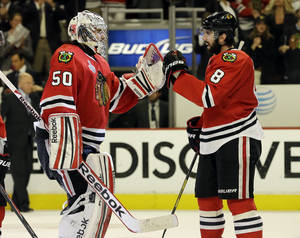 Photo - Chicago Blackhawks goalie Corey Crawford (50) celebrates with defenseman Nick Leddy (8) during the third overtime period of Game 1 in their NHL Stanley Cup Final hockey series, Thursday, June 13, 2013, in Chicago. (AP Photo/Nam Y. Huh)