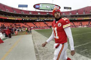 Photo - Kansas City Chiefs quarterback Alex Smith walks off the field after an NFL football game against the Indianapolis Colts on Sunday, Dec. 22, 2013, in Kansas City, Mo. The Colts won 23-7. (AP Photo/Charlie Riedel)