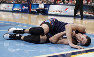 photo - Charlotte Bobcats center Byron Mullens reacts injuring his leg while contesting a shot against the Denver Nuggets late in the fourth quarter of the Nuggets' 110-88 victory in an NBA basketball game in Denver, Saturday, Dec. 22, 2012. Mullens was helped off the court by teammates. (AP Photo/David Zalubowski)
