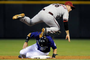Photo -   Arizona Diamondbacks shortstop John McDonald (16) kicks Colorado Rockies' Tyler Colvin (21) in the head after completing the double play to end the first inning of a baseball game, Monday, Sept. 24, 2012, in Denver. Chris Nelson was out at first. (AP Photo/Jack Dempsey)