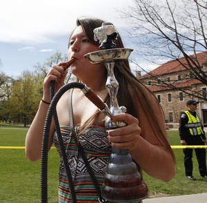 Photo -   A student uses a water pipe to smoke marijuana outside the police barrier on the Norlin Quad at the University of Colorado in Boulder, Colo., on Friday, April 20, 2012. Police blocked off the quad to prevent a 420 marijuana smoke out. (AP Photo/Ed Andrieski)