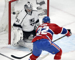Photo - Los Angeles Kings goalie Martin Jones (31) makes the save against Montreal Canadiens left wing Travis Moen during the first period of an NHL hockey game in Montreal on Tuesday, Dec. 10, 2013. (AP Photo/The Canadian Press, Ryan Remiorz)