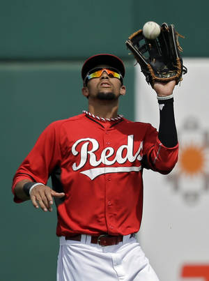 Photo - Cincinnati Reds center fielder Billy Hamilton catches a fly ball off the bat of Milwaukee Brewers' Khris Davis in the second inning of a spring exhibition baseball game Sunday, March 23, 2014, in Goodyear, Ariz. (AP Photo/Mark Duncan)