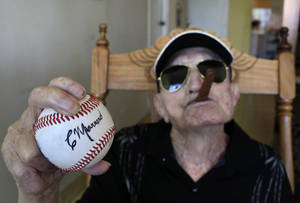 Photo - In this April 23, 2013 photo, Cuba's former pitcher Conrado Marrero, the world's oldest living former major league baseball player, holds up a baseball with his signature at his home, two days before is 102nd birthday, as he holds an unlit cigar in his mouth in Havana, Cuba. In addition to his longevity, the former Washington Senator has much to celebrate this year. After a long wait, he finally received a $20,000 payout from Major League baseball granted to old-timers who played between 1947 and 1979. The money had been held up since 2011 due to issues surrounding the 51-year-old U.S. embargo on Cuba, which prohibits most bank transfers to the Communist-run island. But the payout finally arrived in two parts, one at the end of last year, and the second a few months ago, according to Marrero's family. (AP Photo/Franklin Reyes)