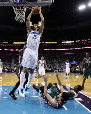 photo - New Orleans Hornets center Robin Lopez (15) shoots as small forward Al-Farouq Aminu and Milwaukee Bucks small forward Ersan Ilyasova (7) fall to the floor in the second half of an NBA basketball game in New Orleans, Monday, Dec. 3, 2012. The Hornets won 102-81. (AP Photo/Gerald Herbert)