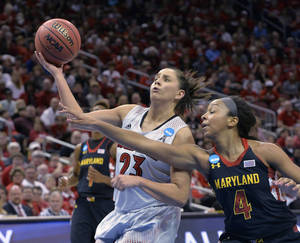 Photo - Maryland's Lexie Brown, right, attempts to knock the ball away from Louisville's Shoni Schimmel during the second half in a regional final of the NCAA women's college basketball tournament Tuesday, April 1, 2014, in Louisville, Ky. Maryland won 76-73. (AP Photo/Timothy D. Easley)