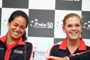 photo - United States' Jamie Hampton, left, and teammate Melanie Oudine smile as they listen to reporter's question after their draw for their World Group first round Fed Cup tennis match against Italy, in Rimini, Italy, Friday, Feb. 8, 2013. The United States is scheduled to face Italy in this weekend's Fed Cup matches. (AP Photo/Felice Calabro')