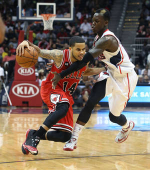 Photo - Chicago Bulls guard D.J. Augustin (14) drives against Atlanta Hawks guard Dennis Schroder (17) in the second half of an NBA basketball game Wednesday, April 2, 2014, in Atlanta. The Bulls won 105-92. (AP Photo/Jason Getz)