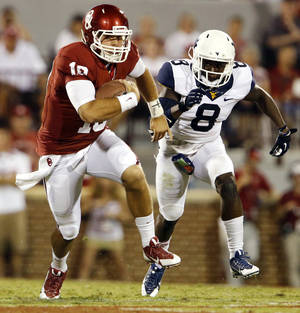 Photo - Oklahoma's Blake Bell (10) runs past Karl Joseph during the second half of a college football game between the University of Oklahoma Sooners (OU) and the West Virginia University Mountaineers at Gaylord Family-Oklahoma Memorial Stadium in Norman, Okla., on Saturday, Sept. 7, 2013. Photo by Steve Sisney, The Oklahoman