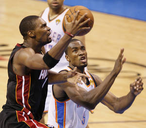 Photo - Miami's Chris Bosh (1) goes past Oklahoma City's Serge Ibaka (9) during Game 2 of the NBA Finals between the Oklahoma City Thunder and the Miami Heat at Chesapeake Energy Arena in Oklahoma City, Thursday, June 14, 2012. Photo by Nate Billings, The Oklahoman
