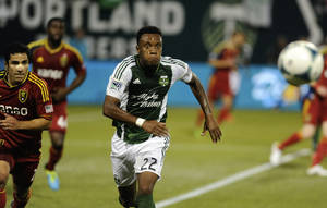Photo - Portland Timbers' Rodney Wallace (22)  chases a ball against Real Salt Lake's Tony Beltran (2) during the first half of an MLS Soccer game in Portland, Ore., Wednesday August 21, 2013.  (AP Photo/Greg Wahl-Stephens)