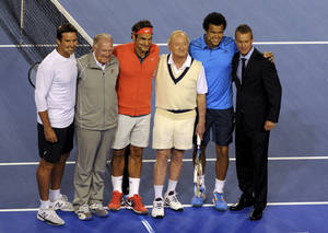 Photo - CORRECTS SPELLING OF ROCHE - Roger Federer, third left, of Switzerland, Jo-Wilfried Tsonga, second right, of France and Lleyton Hewitt, right, of Australia, pose with former Australian tennis greats, Tony Roche, second left, Rod Laver, third right, and Pat Rafter, left, during a gala charity exhibition match in the lead up to the Australian Open at Rod Laver Arena in Melbourne, Australia, Wednesday, Jan 8, 2014. The charity event for the Roger Federer Foundation and the Australian Tennis Foundation will raise money for the education of African children. (AP Photo/Mal Fairclough)