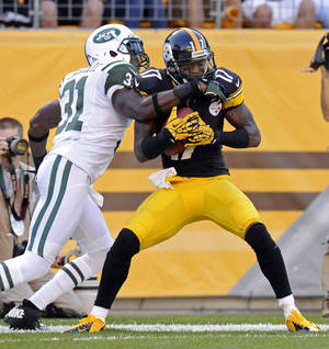 Photo -   Pittsburgh Steelers wide receiver Mike Wallace (17) is hit by New York Jets cornerback Antonio Cromartie (31) after making a catch for a touchdown in the third quarter of an NFL football game on Sunday, Sept. 16, 2012, in Pittsburgh. The touchdown call was confirmed after a video review.(AP Photo/Don Wright)