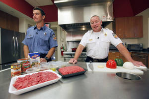 Photo - Edmond Firefighter Lindall Wood, left, and Battalion Chief Doug Hall while recording their cooking show on how to make firehouse chili. Fire Prevention Week begins Oct. 6. PHOTO BY PAUL HELLSTERN, THE OKLAHOMAN. <strong>PAUL HELLSTERN - OKLAHOMAN</strong>