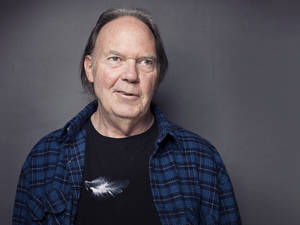 "Photo -   This Sept. 27, 2012 photo shows singer-songwriter Neil Young posing for a portrait at The Carlyle hotel in New York. Young has released his first book, a memoir titled, ""Waging Heavy Peace."" (Photo by Victoria Will/Invision/AP)"