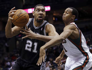 Photo - San Antonio Spurs' Tim Duncan is fouled as he drives past Milwaukee Bucks' John Henson during the second half of an NBA basketball game Wednesday, Dec. 11, 2013, in Milwaukee. (AP Photo/Morry Gash)